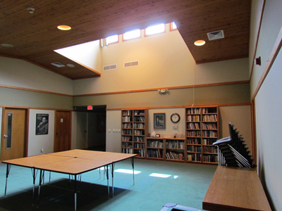 Our Commons area features several tables and chairs, our Library, and both natural and artificial lighting.
